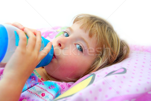 girl drinking bottle of milk laying on bed Stock photo © lunamarina