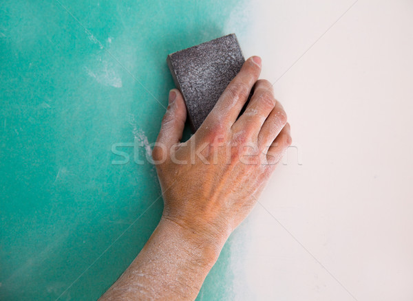 plastering man hand sanding the plaste in drywall seam Stock photo © lunamarina