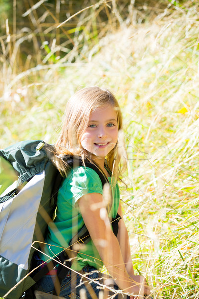 Blond explorer kid girl walking with backpack in grass Stock photo © lunamarina