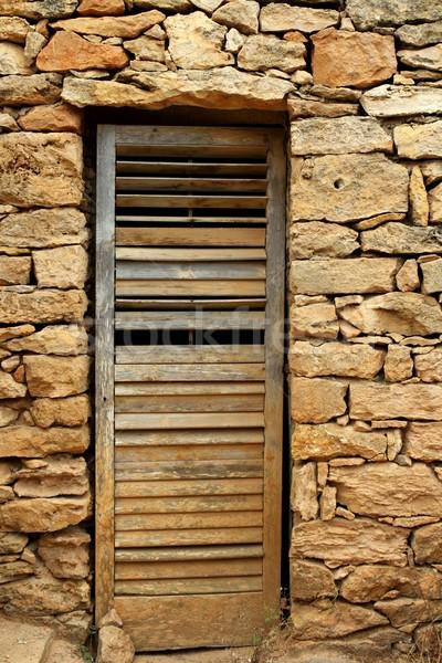 Kopott fa ajtó kőművesmunka kőfal viharvert Stock fotó © lunamarina