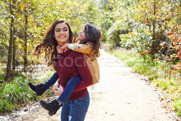 Mother and daughter fun piggyback in a park Stock photo © lunamarina