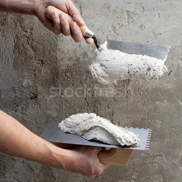 construction notched trowel and worker hands Stock photo © lunamarina