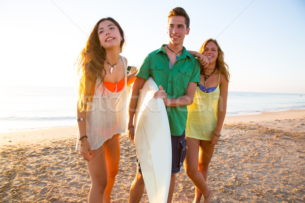Surfer girls with teen boy walking on beach shore Stock photo © lunamarina