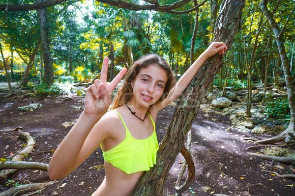 Caucasian girl playing victory sign in jungle Stock photo © lunamarina