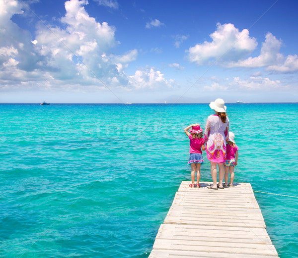 Daughters and mother in jetty on tropical beach Stock photo © lunamarina