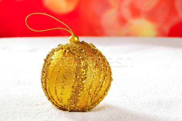 Christmas golden bauble on snow and red Stock photo © lunamarina