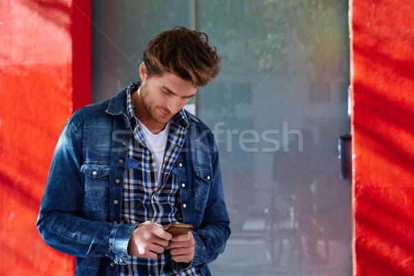 ストックフォト: 若い男 · スマートフォン · 屋外 · ジーンズ · 手 · 通り