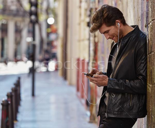 молодым человеком прослушивании музыку смартфон улице Сток-фото © lunamarina
