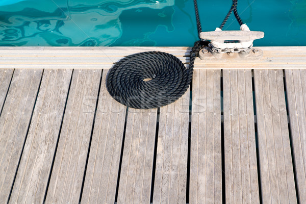 mooring wooden pier with coiled spiral rope and a bitt Stock photo © lunamarina