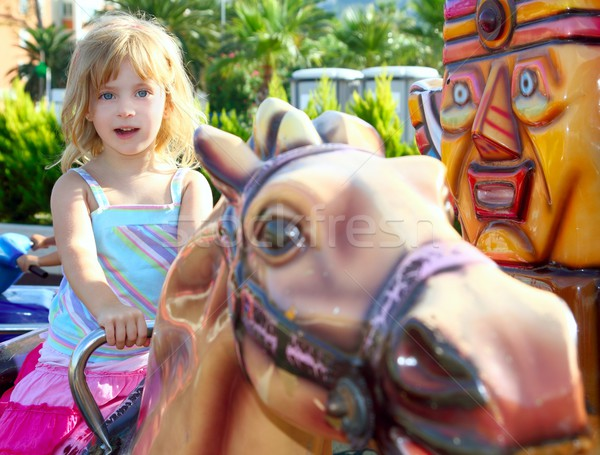 blond girl with fairground horse enjoy in park Stock photo © lunamarina