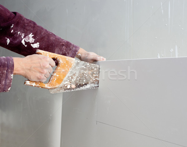 cutting plasterboard plaster hand dirty saw Stock photo © lunamarina