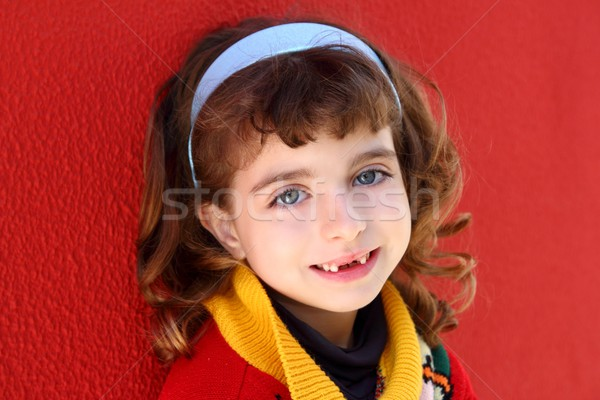 smiling little girl indented front teeth smile on red Stock photo © lunamarina