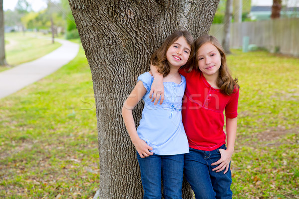 kid friend girls whispering ear playing in a park tree Stock photo © lunamarina