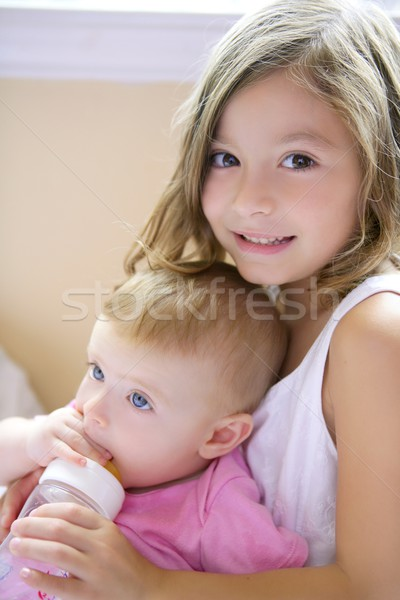 Toddler girl giving bottle of milk to baby sister Stock photo © lunamarina