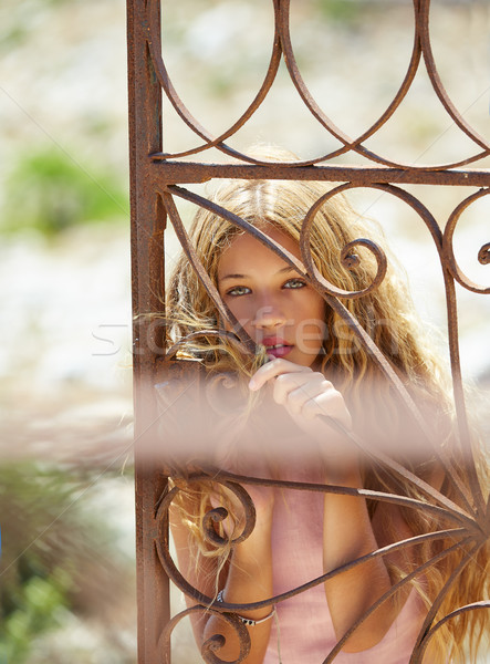 Blond girl in Mediterranean rusted gate at sea Stock photo © lunamarina