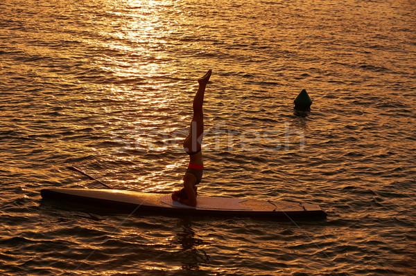 Yoga girl over SUP Stand up Surf board Stock photo © lunamarina