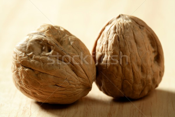 Two walnut with shells over wooden background Stock photo © lunamarina