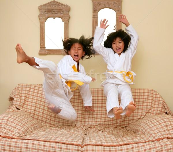 Two little asian judo gils jump on sofa Stock photo © lunamarina