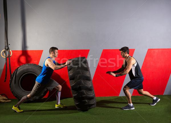 men flipping a tractor tire workout gym exercise Stock photo © lunamarina