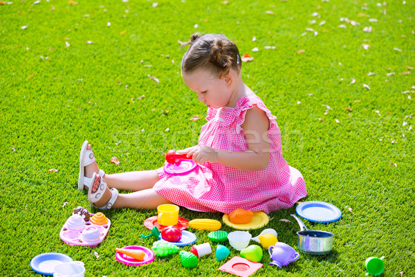 Toddler kid girl playing with food toys sitting in turf Stock photo © lunamarina
