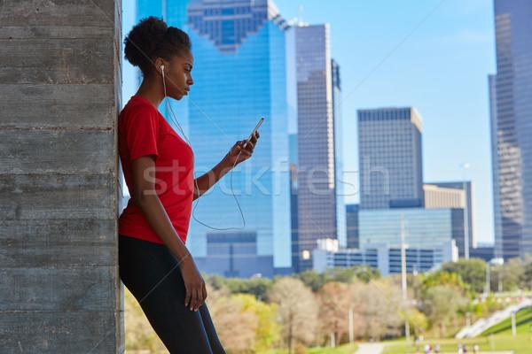 Runner girl hearing music earphones in the city Stock photo © lunamarina