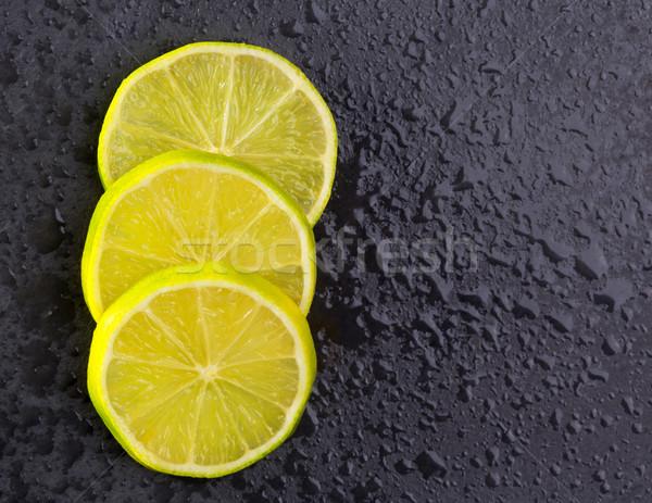 Fresh lima slices with water drops on black Stock photo © lunamarina