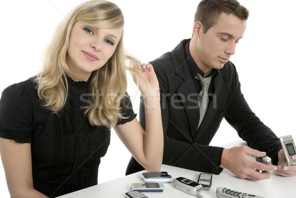 Business couple with many mobile telephones Stock photo © lunamarina
