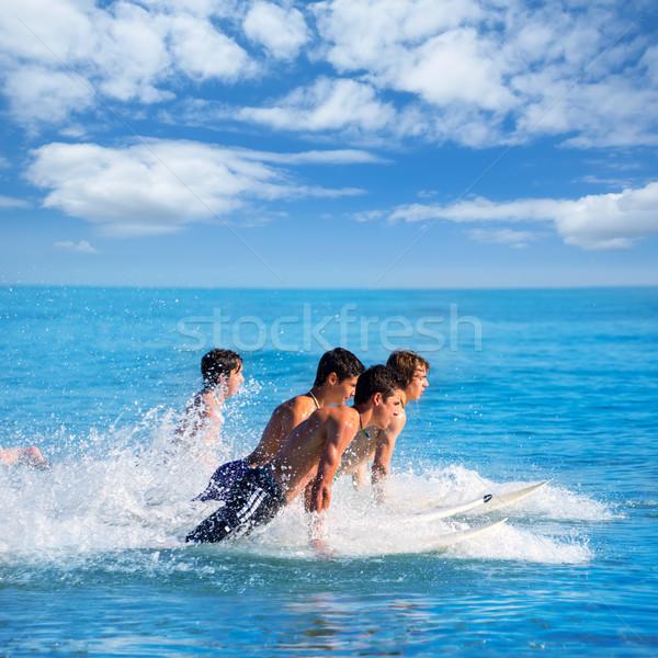Boys surfers surfing running jumping on surfboards Stock photo © lunamarina