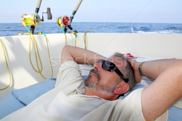 Sailor senior fisherman relax on boat fishing sea Stock photo © lunamarina