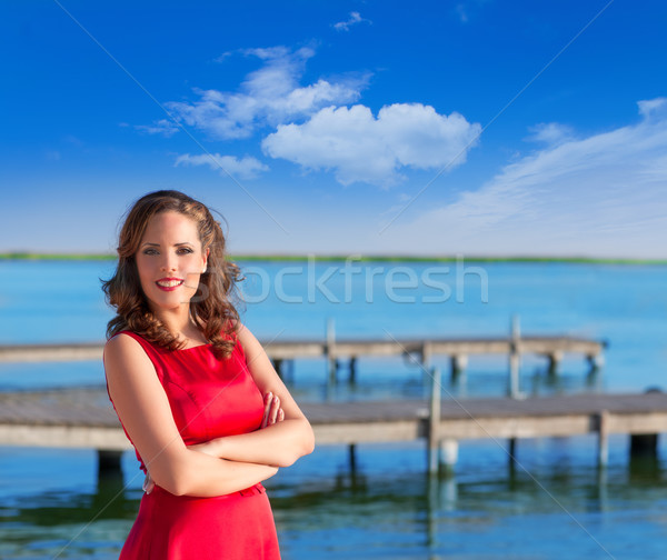 Brunette woman dress in red smiling relaxed on a lake Stock photo © lunamarina