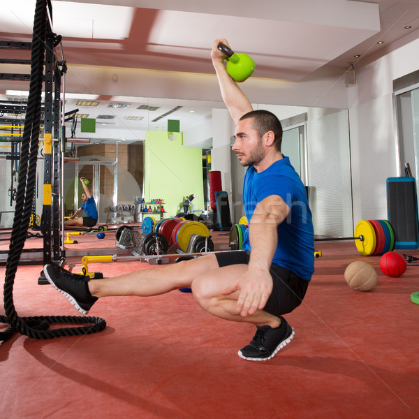 Crossfit fitness man balance Kettlebells with one leg Stock photo © lunamarina
