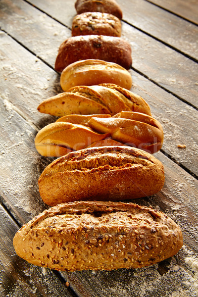 Breads varied in a row on rustic wood and flour Stock photo © lunamarina