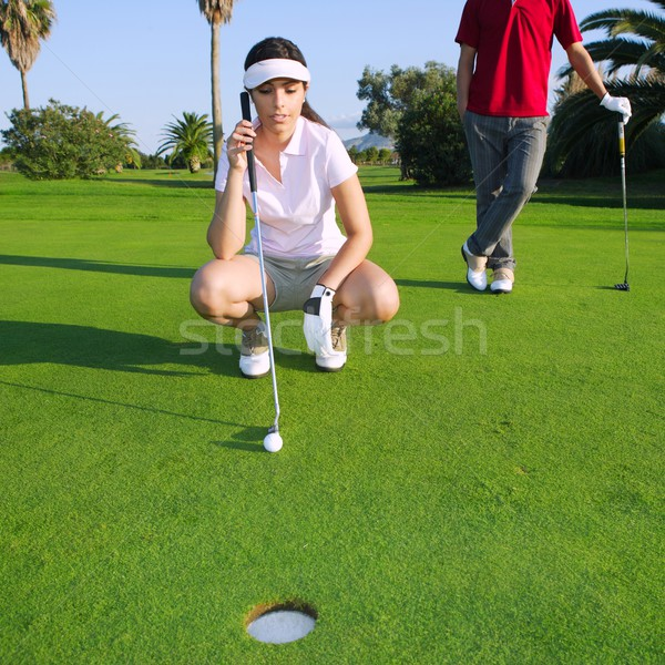 golf young woman looking and aiming the hole Stock photo © lunamarina