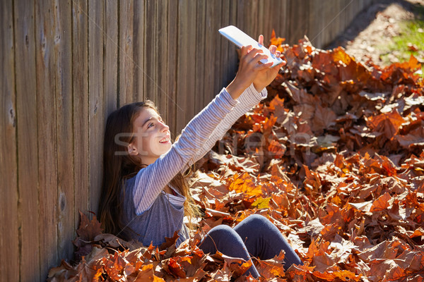 Tween kid girl selfie tablet pc in autumn leaves Stock photo © lunamarina