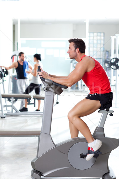 man on stationary bicycle at sport fitness gym Stock photo © lunamarina