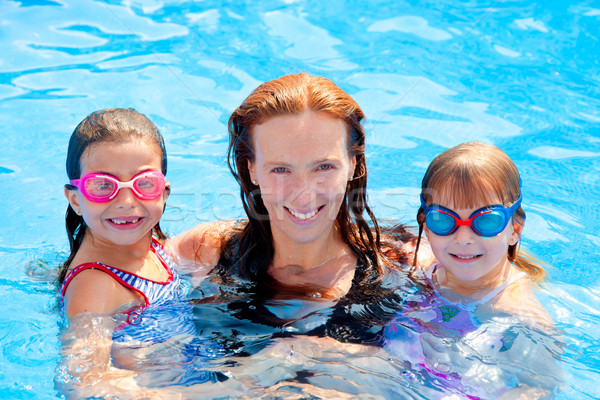daughters and mother family swimming in pool Stock photo © lunamarina