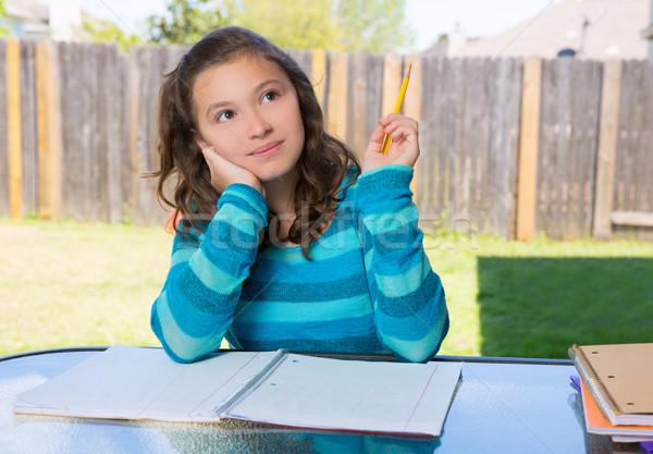 American latin teen girl doing homework on backyard Stock photo © lunamarina