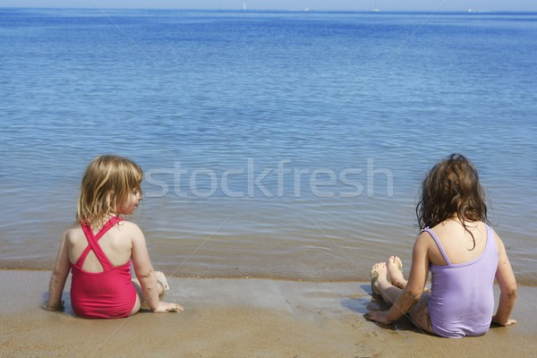 tow sisters sit on beach bathing suit swimsuit Stock photo © lunamarina