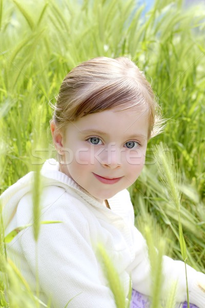 happy blond little girl sit on green spikes meadow Stock photo © lunamarina