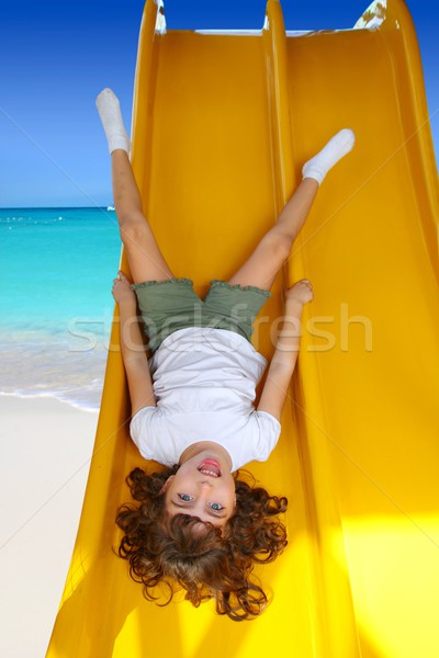 Brunette little girl upside down playground slide Stock photo © lunamarina