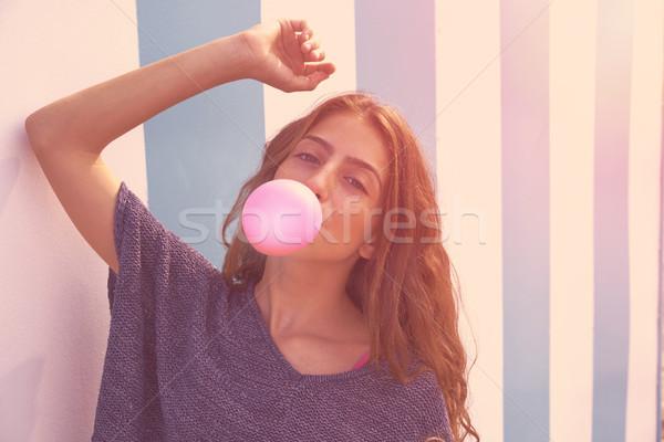Brunette teen girl bubble gum in blue stripes wall Stock photo © lunamarina