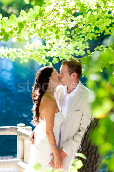 couple in love kissing in forest tree blue lake Stock photo © lunamarina