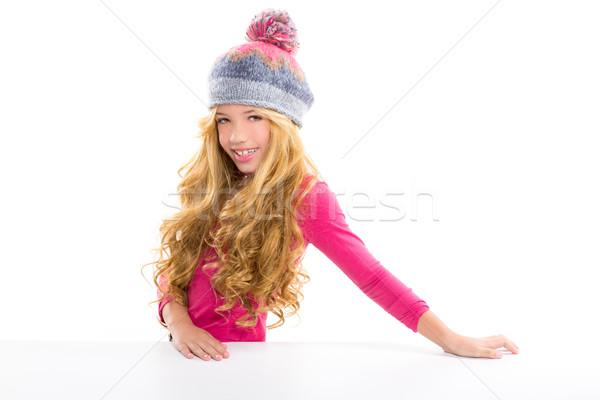Kid girl with winter wool cap smiling on white Stock photo © lunamarina