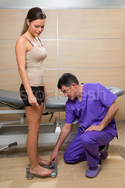 Doctor checking weight scale measure of woman patient Stock photo © lunamarina