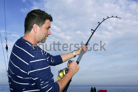 Angler fisherman fighting big fish rod and reel Stock photo © lunamarina