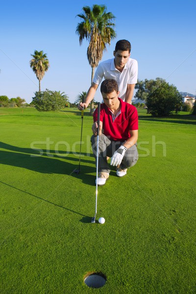 golf young man looking and aiming the hole Stock photo © lunamarina