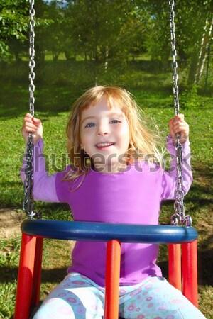 girl swinging on swing happy in meadow grass park Stock photo © lunamarina