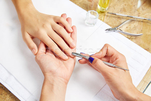 Cuticle pusher tool in nails salon woman hands Stock photo © lunamarina