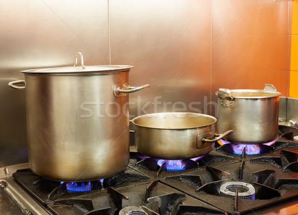 Restaurant pro kitchen with steel pans in fire Stock photo © lunamarina