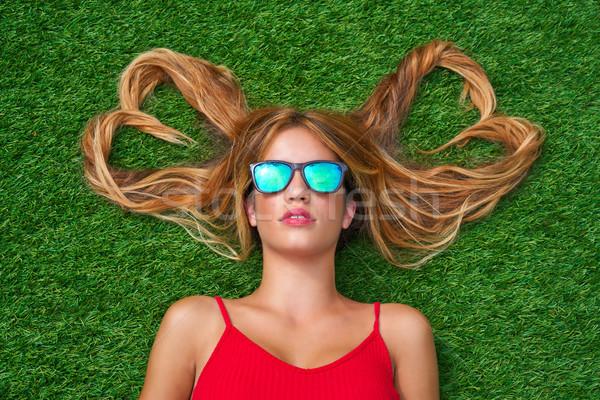 Blond teen girl with hair heart shapes lying Stock photo © lunamarina